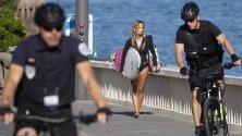 Патрул на жандармерията минава край сърфистка във френския град Биариц, където се провежда срещата на Г-7, докато тече пиковия летен сезон.