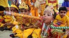 Деца от държавно училище облечени като бог Кришна и богиня Радха по време на фестивала Джанмашти, отбелязващ рождението на Кришна, в Бопал, Индия.