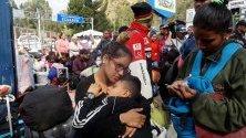 Семейство от Венецуела почива докато преминава границата между Колумция и Еквадор. Над 11 000 венецуелци са напуснали Колумбия само през уикенда през граничния пункт.