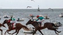 Жокеи се надпреварват с конете си по време на първия ден от 174-тите конни състезания на плажа Санлукар де Барамеда, Кадис, Испания.