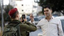 Израелски войници проверяват паспорта на палестински шофьор на КПП в Хеброн.