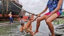 Деца във Филипините си играят край кораб в пристанищетона Манила в очакване на тропическата буря Подул, която се приближава с ветрове от 80 км/ч.
