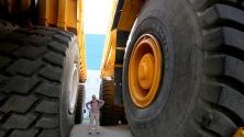 Посетител между гумите на два 450-тонни камиони на беларуската компания BelAZ, предназначени за минодобив.