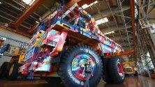 Жена позира пред камуфлажен 90-тонен камион на беларуската BelAZ и компанията за видеоигри Wargaming. Много работници на BelAZ играят играта `World of tanks` и от там дошла идеята за сътрудничеството.