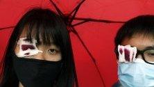 Ученици от Хонконг са покрили очите си очите си в солидарност с жена, пострадала в окото по време на сблъсъци с полицията.