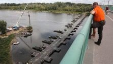 Полски войници изграждат временна канализация през понтонен мост, за да се спрат боклуците, изхвърляни в река Вистула след аварията в канализацията във Варшава.