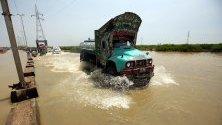 Камион преминава през наводнен път след проливни дъждове в Карачи, Пакистан.