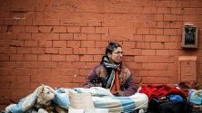 Бездомник и кучето му по време на демонстрации в Буенос Айрес, Аржентина. Кризата подбуди социално напрежение и синдикални протести.