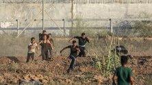 Палестинчета бягат по време на сблъсъци на границата между Израел и Газа.
