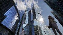 Хора  минават покрай кулите на бизнес центъра Москва Сити в Москва, Русия.