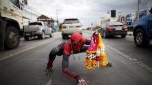 Уличен търговец в Тайланд продава стоката си в костюм на Спайдърмен.