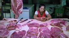 Продавач на свинско месо в Пекин, Китай. Властите пускат тонове замразено свинско от държавния резерв, след като Пекин унищожи над 1 милион прасета в опит да ограничи африканската чума.