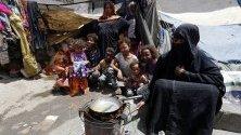 Жена приготвя храна на деца във временен лагер в Сана, Йемен. Конфликтът между бунтовниците хути и правителствените части от 2015 г. досега е довел до над 3,6 милиона бежанци.
