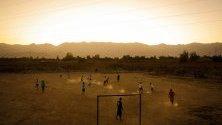 Деца играят футбол в поле край селото им в покрайнините на Кабул, Афганистан.