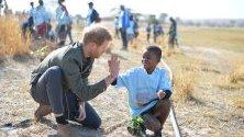 Принц Хари с местно дете в резерват в Ботсвана.