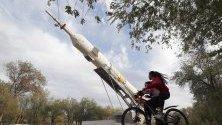 """Дете на велосипед пред монумент на ракетата """"Союз"""" в Байконур, Казахстан. Градът е създаден през 1955 г., за да обслужва космодрума Байконур."""