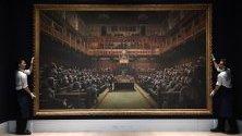 """Подготовка на аукцион на съвременно изкуство в """"Сотбис"""" в Лондон. Куратори подготвят картина на Банкси """"Devolved Parliament""""."""