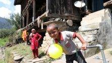 Деца играят край традиционна къща в село Бараграм, Индия. Бараграм лежи на брега на река Ул, заобиколено от планинската верига Дауладар и е важен пункт за почивка на планинските катерачи.