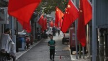 Китайски национални знамена в квартал Хутонг в Пекин. Страната се готви да отбележи утре 70-годишнината от основаването на народната република.
