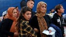 Семейство мигранти чака на пристанището в Пирея, Гърция, след пристигането си с ферибот от бежанския лагер на остров Лесбос. Те ще бъдат преразпределени в различни центрове из страната заради препълването на лагера.