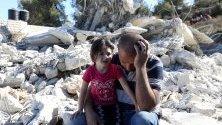 Палестинец и детето му седят край разрушена от израелските части постройка в Биет Омар, на Западния бряг. Израелската армия регулярно разрушава палестински сгради в района поради липса на разрешение за строеж.