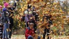 Деца играят сред листата в парк Остафиево в Москва.