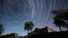 Дълга експозиция на звезди над параклис в град Комийас, Испания, заснета по време на Драконидите - първите метеорни потоци през есента.