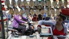 Текстилна работничка купува храна на уличен пазар в Пном Пен. Минималната работна заплата на текстилните работници е нараснала от 170 на 190 долара.