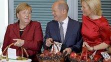 """Германският канцлер Ангела Меркел, финансовият министър Олаф Шолц и земеделският Юлия Кльокнер представят ябълкова продукция по време на годишната """"ябълкова"""" среща на кабинета."""