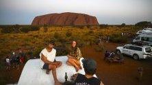 Туристи се снимат на фона на Улуру - вторият по големина скален монолит на планетата, Северните територии на Австралия.