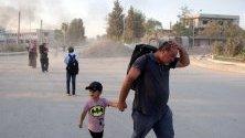 Кюрдско семейство бяга от дома си в град Рас Ал-Ейн по време на турската офанзива в Северна Сирия.