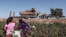 """Работници събират памук докато по пътя преминават турски части от операцията """"Извор на мира"""" в Северна Сирия."""