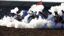 """Ездачи стрелят с пушки с барут по време на националното състезание """"Табурида"""" - традиционна конска надпревара в Ел Джадида, Мароко."""