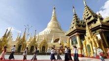 Хора носят на носилка момче, подготвяно за монах, по време на посещението му в пагодата Шуедагон, Янгон, Мианмар.