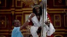 Мъж пали свещ пред статуя на Черния Исус от Портобело (Cristo Negro de Portobelo) в едноименния град в Панама.