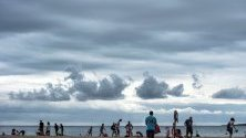 Хора на плажа Пунта Прима в Сант Луис в Менорка, Балеарските острови. Прогнозите са за дъжд и вятър в региона.