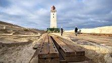 Подготовка за преместване на фара в Ютланд, Дания. Фарът ще бъде преместен заради ерозия на брега. За целта се използват ролкови релси.