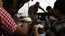 Сирийски бежанци-кюрди получават храна в бежански лагер в Иракски Кюрдистан. Хиляди бежанци пристигат от началото на операцията на Турция в Сирия.