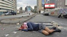 Протестиращ спи на земята край блокада на улица в Бейрут, Ливан. Демонстрациите и блокирането на пътища ще продължат до оставка на правителството и парламента.
