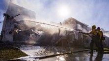 Пожарникари гасят запалила се къща по време на горските пожари край Санта Кларита, Калифорния.