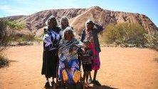 Аборигени, собственици на земята в района, позират пред скалния масив Улуру в Австралия в деня, в който вече е забранено на туристите да се катерят по него.