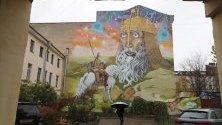 Жена минава край двор с изрисувани графити в центъра на Санкт Петербург. Есенните температури в града достигнаха 10 градуса.