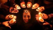 Индийка позира до свещи по време на фестивала Дивали в Бопал, Индия. Светлините по време на фестивала символизират победата на доброто над злото.