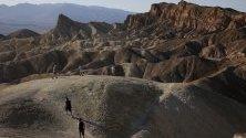 Туристи се разхождат по Забриски Пойнт в пустиня в националния парк Death Valley в Калифорния. Това е едно от най-горещите и сухи места в света.