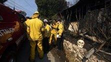 Пожарникари оглеждат щетите по изгоряла къща, декорирана за Хелоуин, край Лос Анджелис, Калифорния. В района е обявена евакуация.