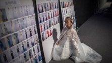 Младо дете - модел разглежда табло със снимки на други модели и облеклото им в бекстейджа преди дефиле по време на Седмицата на модата в Пекин, Китай.