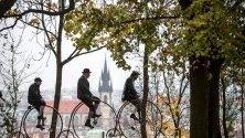 """Участници в традиционната надпревара """"Пражката миля"""", облечени в исторически дрехи, карат високи колела (пени фартинг), Прага."""