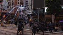 Сълзотворен газ експлодира над протестиращи по време на демонстрация в Хонконг, Китай. Протестите продължават пети месец.