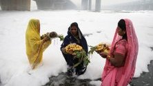 Индийски вярващи изпълняват ритуали в замърсената река Ямуна, покрита с токсична пяна от близкия завод, по време на фестивала Чат Пуджа в Ню Делхи, Индия.