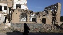Жена минава край разрушена сграда, бомбардирана по време на водените от Саудитска арабия нападения над Сана, Йемен. Страната е във въоръжен конфликт от края на 2014 г.